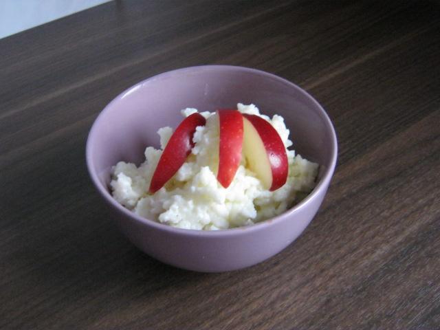 orez cu lapte ornat cu felii rosii de mere ionatan intr-un bol mic mov