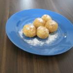cinci galuste cu branza presarate cu zahar praf (vanilat) pe o farfurie plata albastra pe blatul de bucatarie maro
