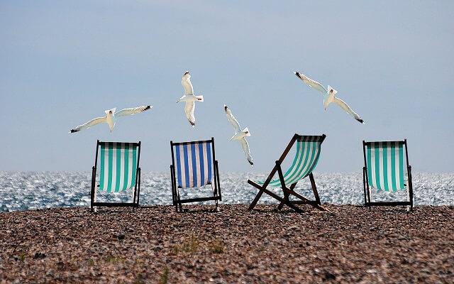 vacanta, plaja cu nisip fin, sezlonguri langa mare, pescarusi zburatori