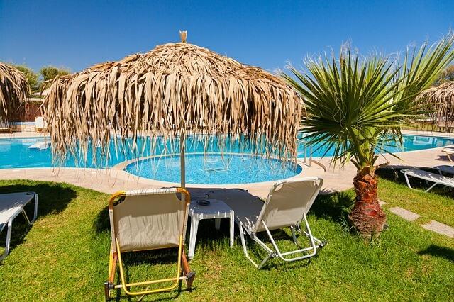 vacanta all inclusive pret, bazinul unui hotel plin de apa cu sezlonguri pe mal, plasate pe iarba verde cu palmieri imprejur si cu cerul albastru si senin