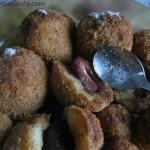 galuste cu prune umplute cu jumatati de prune, formate cu mana in bilute, rostogolite in pesmet prajit si puse pe o farfurie, servite cu zahar pudra si scortisoara